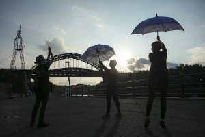 Dancers rehearse in the sunshine with umbrellas. Portolan, Sunderland Tall Ships, Cirque Bijou. Image Dan Prince.