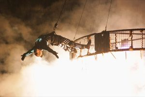 A performer hangs from the aerial crane in the skiy.