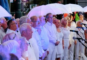 A choir complete with LED umbrellas perform. Portolan, Sunderland Tall Ships, Cirque Bijou. Image Sunderland City Council.