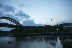 A landscape shot showing the River Weir and Wearmouth Bridge and performer Chris Bullzini walking along the wire. Portolan, Sunderland Tall Ships, Cirque Bijou. Image Dan Prince.