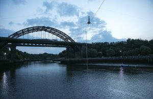 Performer Chris Bulzini does a handstand on the wire over the River Weir. Portolan, Sunderland Tall Ships, Cirque Bijou. Image Dan Prince.