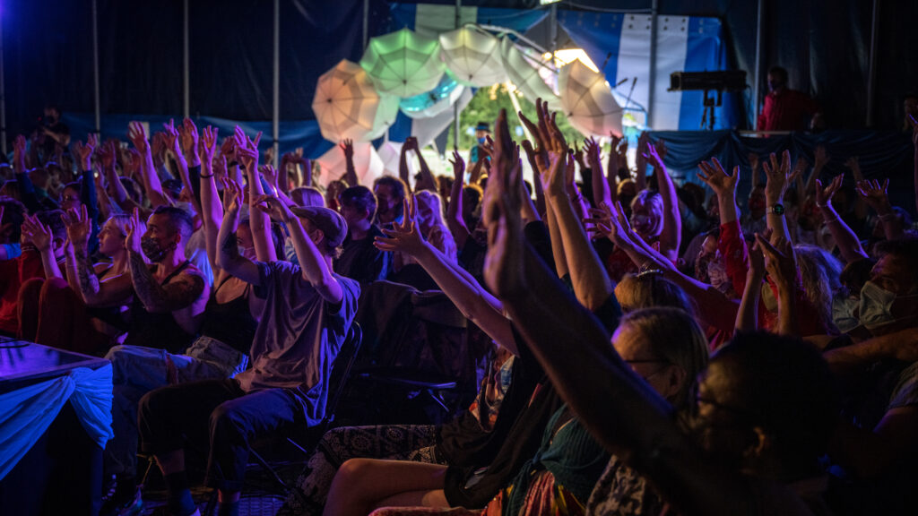 An audience wearing masks have their hands up in their air, facing towards a stage off screen.  They are in a Big Top tent with an entrance way  with an arch of colourfully lit umbrellas
