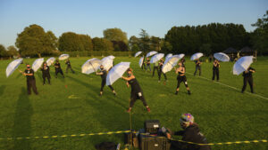 A field of distanced dancers hold white umbrellas up in a synchronised movement, green grass and blue sky