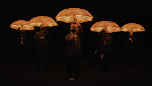 A phalanx of people advance holding glowing red umbrellas above their heads against a dark background. Their mouths and noses are hidden behind masks
